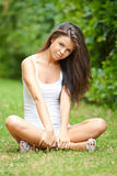 Relaxed beautiful brunette sitting on grass Royalty Free Stock Image