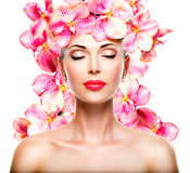 Relaxed beautiful face of a young girl with clear skin and pink. Orchids. Beauty treatment concept Stock Photography