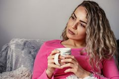 Relaxed beautiful girl drink coffee on a comfortable couch. At home Royalty Free Stock Photos