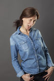 Relaxed beautiful middle aged woman winking with hands in pockets Stock Photography