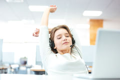 Relaxed beautiful woman sitting and stretching on workplace Stock Photo