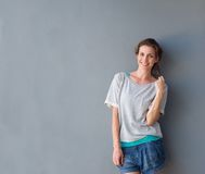 Relaxed beautiful woman smiling against gray background Royalty Free Stock Photography