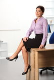 Relaxed beautiful young business woman sitting on Royalty Free Stock Images