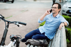 Relaxed bespectacled man speaking on cellphone. Glad to hear you. Satisfied handsome man smiling and having conversation on cellphone while sitting on the bench Royalty Free Stock Photos