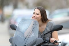 Relaxed biker on her motorbike thinking. Relaxed biker sitting on her motorbike thinking and looking away on the street Stock Photos