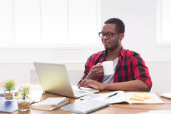 Relaxed black businessman in casual office, work with laptop, drink coffee. Relaxed black businessman in office, in casual, work with laptop, drink coffee royalty free stock photos