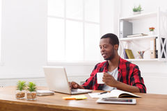 Relaxed black businessman in casual office, work with laptop, drink coffee. Relaxed black businessman in office, in casual, work with laptop, drink coffee stock image