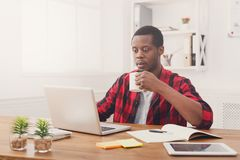 Relaxed black businessman in casual office, work with laptop, drink coffee. Relaxed black businessman in office, in casual, work with laptop, drink coffee royalty free stock images