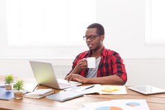 Relaxed black businessman in casual office, work with laptop, drink coffee. Relaxed black businessman in office, in casual, work with laptop, drink coffee stock photos