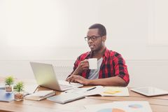 Relaxed black businessman in casual office, work with laptop, drink coffee. Relaxed black businessman in office, in casual, work with laptop, drink coffee stock photo