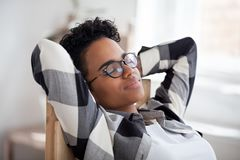 Relaxed black woman resting taking break holding hands behind head stock photo