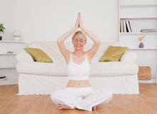 Relaxed blond-haired woman practicing yoga Stock Photos