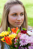Relaxed blonde girl holding a bunch of flowers Royalty Free Stock Images