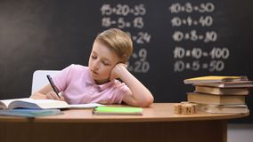 Relaxed bored schoolboy sitting at desk, unwilling to prepare math homework. Stock footage stock video