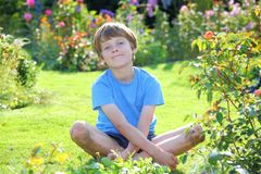 Relaxed boy. Portrait of a relaxed young teenage boy in the garden Royalty Free Stock Image