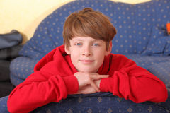 Relaxed boy. Portrait of a relaxed young boy sitting on a sofa Royalty Free Stock Images