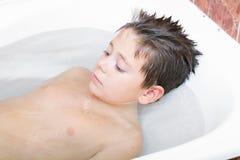 Relaxed boy in bath. Relaxed boy laying down in bath looking sideways Royalty Free Stock Photo