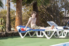 Relaxed boy enjoys lying on. The couch in the pool area Royalty Free Stock Images