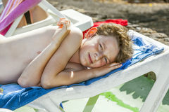 Relaxed boy enjoys lying on. The couch in the pool area Stock Photography