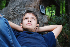 Relaxed boy with a gadget Royalty Free Stock Images
