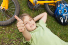 Relaxed boy gesturing thumbs up at park. High angle portrait of a relaxed boy gesturing thumbs up at the park Stock Image