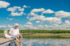 Relaxed boy with his father on a fishing trip. On a beautiful lake Stock Images