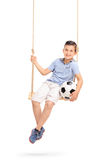 Relaxed boy holding football seated on a swing. Vertical shot of a relaxed and joyful little boy holding a football seated on a wooden swing isolated on white Royalty Free Stock Image