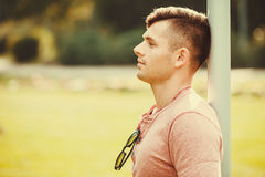 Relaxed boy leaning on pole. Masculinity handsome outdoor concept. Relaxed boy leaning on pole. Young man chilling in park Royalty Free Stock Images