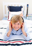 Relaxed boy listening music lying down on bed. With headphones Stock Image
