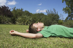Relaxed Boy Listening To MP3 Player On Grass. Side view of a young boy resting on grass and listening to MP3 player Royalty Free Stock Photos