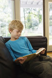 Relaxed Boy Reading Book On Sofa. Relaxed young boy sitting on sofa with book in living room Stock Images