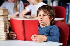 Relaxed Boy Reading Book At Table In Library. Relaxed little schoolboy reading book while sitting at table in library Stock Photos
