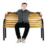Relaxed boy sitting on bench. Isolated Royalty Free Stock Photos