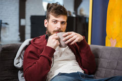 Relaxed boy sitting on sofa and drinking coffee. Relaxed handsome boy sitting on grey sofa and drinking coffee Royalty Free Stock Photography