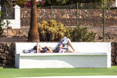 Relaxed boy sleeping at the bench. Relaxed boy sleeping on the bench in the pool area Stock Photos
