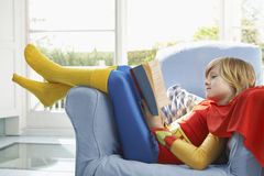 Relaxed Boy In Superman Costume Reading. Side view of a relaxed young boy in superman costume reading book on armchair Royalty Free Stock Photography