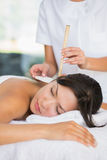 Relaxed brunette getting an ear candling treatment Stock Images