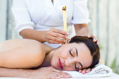 Relaxed brunette getting an ear candling treatment Royalty Free Stock Photos