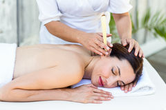 Relaxed brunette getting an ear candling treatment Royalty Free Stock Images