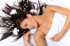 Relaxed brunette girl with white petals in hair Stock Photography