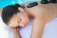 Relaxed brunette lying poolside having a hot stone massage Stock Photography