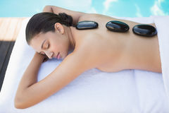Relaxed brunette lying poolside having a hot stone massage Royalty Free Stock Photos