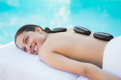 Relaxed brunette lying poolside having a hot stone massage Stock Photos
