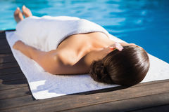 Relaxed brunette lying on a towel poolside Stock Photos