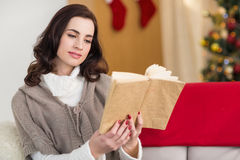 Relaxed brunette reading on the couch at christmas Stock Image