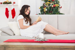 Relaxed brunette reading on the couch at christmas Royalty Free Stock Photos