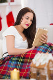 Relaxed brunette reading on the couch with cover Stock Images
