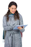 Relaxed brunette wearing winter clothes holding her tablet Stock Photo