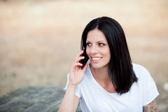 Relaxed brunette woman on the park with mobile Stock Photography