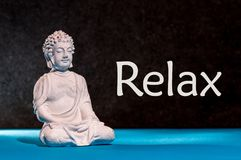 Relaxed buddha figurine sitting and meditating, doing yoga exersice. Relax - inscription.  Royalty Free Stock Photo